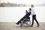 Caretaker pushing disabled man on wheelchair along lake - MASF05860