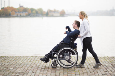 Caretaker pushing disabled man on wheelchair along lake - MASF05860