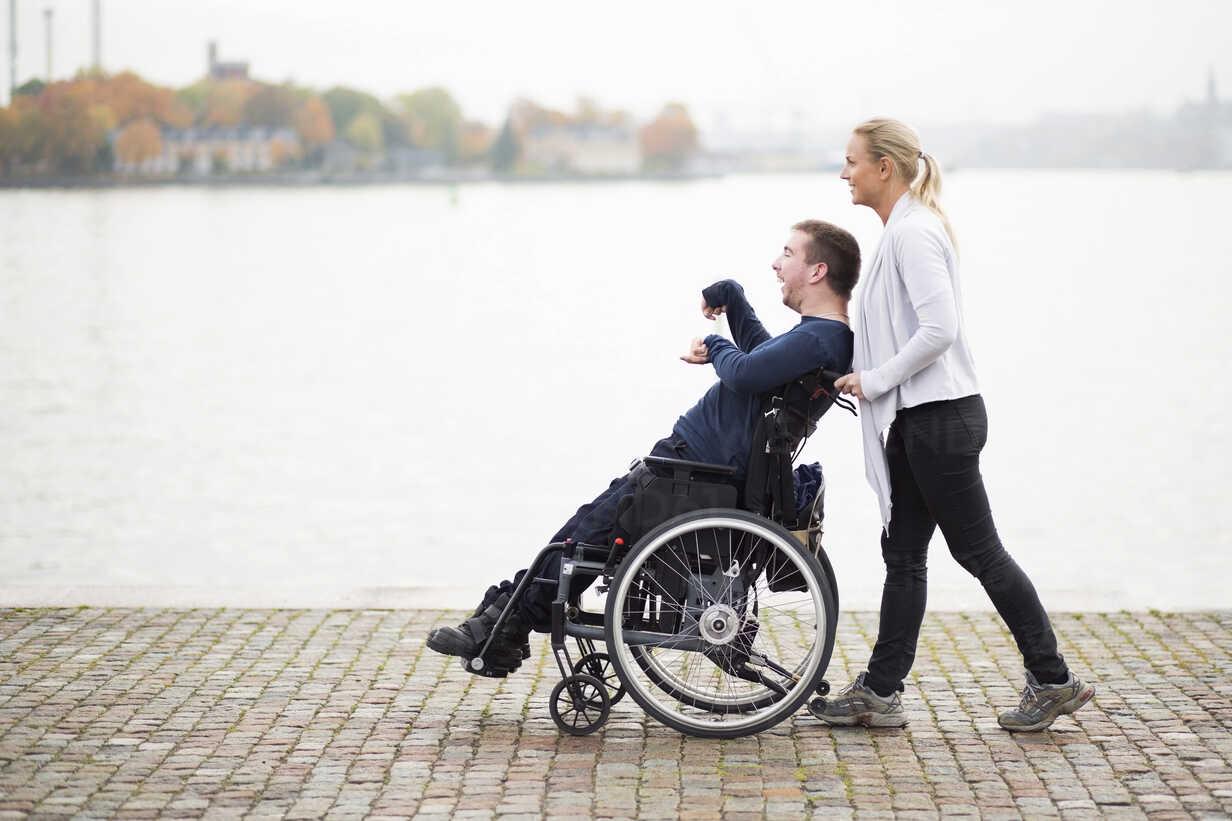 Caretaker pushing disabled man on wheelchair along lake - MASF05860 - Maskot ./Westend61