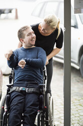 Caretaker talking to disabled man on wheelchair outdoors - MASF05863