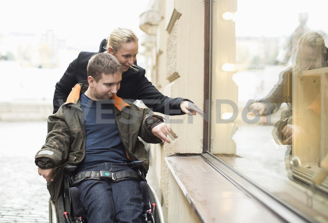 Disabled man on wheelchair widow shopping with caretaker - MASF05866