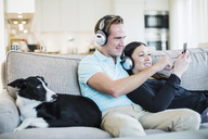 Couple listening to headphones with dog sitting on sofa - MASF05884
