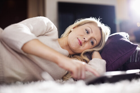 Young woman using digital tablet while lying in bed - MASF05899