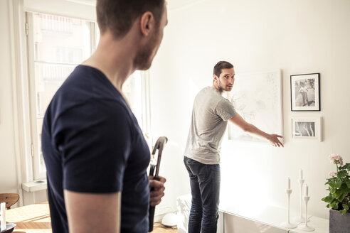Young gay man looking over shoulder at partner while hanging frame on wall in home - MASF05935