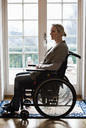 Side view of disabled woman in wheelchair at home - MASF05962