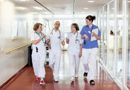 Team of doctors communicating while walking in hospital corridor - MASF05986