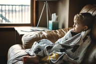 Thoughtful boy wrapped in blanket relaxing on sofa at home - CAVF43465