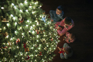 High angle view of siblings sitting by Christmas tree at home - CAVF43480