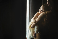 Mother carrying daughter while standing by window at home - CAVF43486