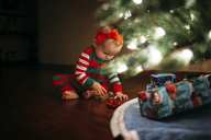 Girl playing with toy while sitting by Christmas tree at home - CAVF43492