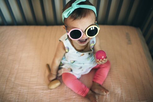 High angle view of playful baby girl wearing sunglasses in crib at home - CAVF43498