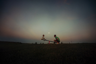 Father and son playing on seesaw against sky at dusk - CAVF43510