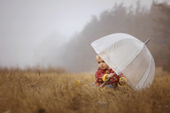 Boy with umbrella sitting on grassy field against sky during foggy weather - CAVF43522