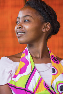 Thoughtful young African woman looking away against orange wall - CAVF43528