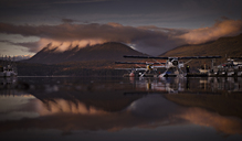 Biplanes parked in lake against mountain during sunset - CAVF43561
