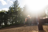 Girl swinging in forest during sunny day - CAVF43627