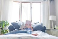 Girl reading book while lying on bed at home - CAVF43645