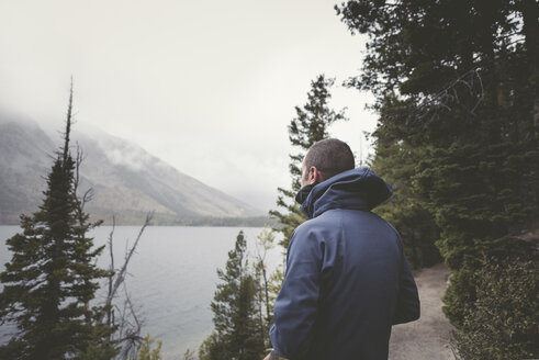 Man in warm clothing looking at view while standing at Grand Teton National Park - CAVF43765