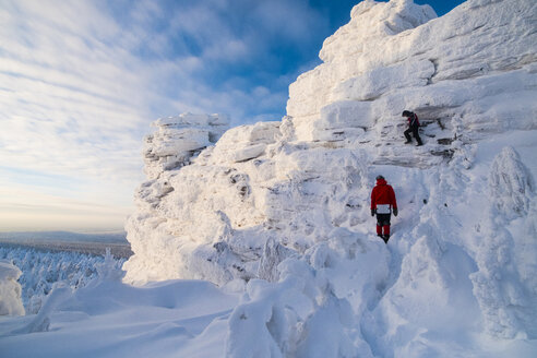 Friends hiking on snow covered mountain against sky - CAVF43858