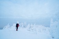 Side view of hiker standing on snow covered fill against cloudy sky - CAVF43861