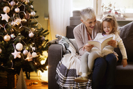 Grandmother and girl reading book while sitting on sofa at home - CAVF43975