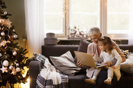 Happy grandmother and granddaughter using laptop while sitting on sofa at home - CAVF43981