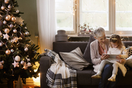 Grandmother assisting granddaughter using tablet computer while sitting on sofa - CAVF43984
