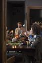 Friends enjoying dinner at table in home - CAVF43999