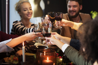 Happy friends toasting wine while enjoying in Christmas party - CAVF44029