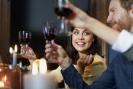 Happy friends toasting wineglasses at home - CAVF44038