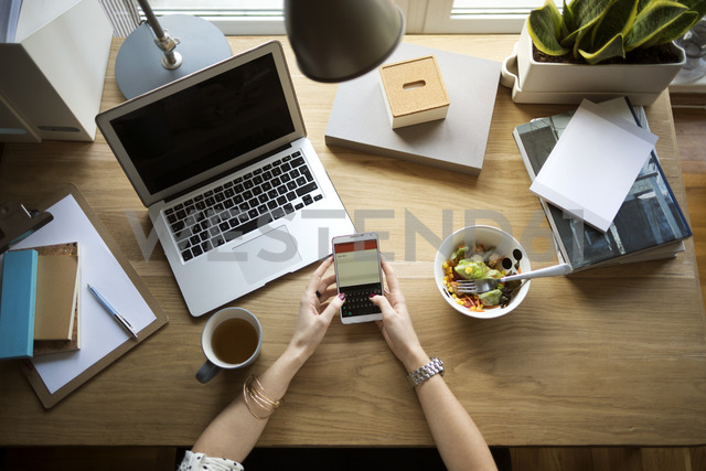 Overhead view of woman using smart phone at desk in home office - CAVF44053