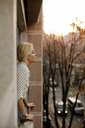 Side view of relaxed woman standing at house window - CAVF44056