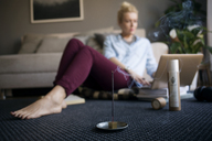 Smoke coming out from incense stick on floor with woman working in background - CAVF44065