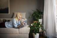 Happy woman using tablet computer while lying on sofa at home - CAVF44068
