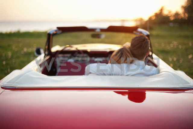 Rear view of young couple with arms around sitting in convertible car at field - MASF06018