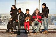 Portrait of young woman with multi ethnic friends using mobile phones on bench - MASF06030