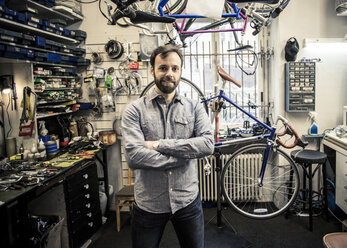 Portrait of mid adult male owner standing arms crossed at bicycle repair shop - MASF06042