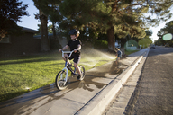 Boy riding bicycle on sidewalk while girl playing with sprinklers - CAVF44098