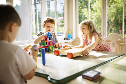Siblings playing with toy blocks at home - CAVF44110
