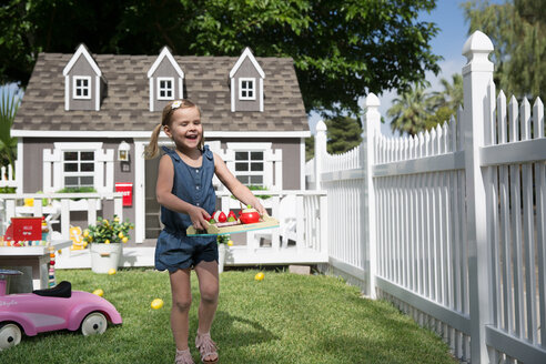 Happy girl holding tray with toys while walking at yard - CAVF44143