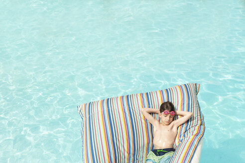 High angle view of boy lying on inflatable raft in swimming pool - CAVF44152