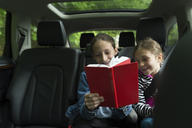 Happy sisters reading book while sitting in car - CAVF44188