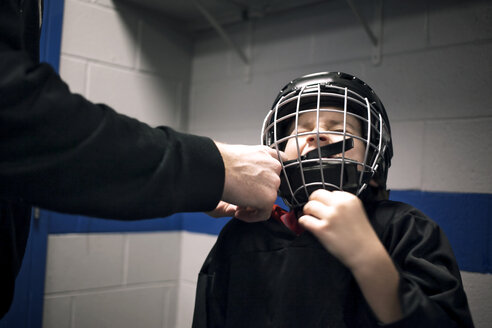 Father helping son with ice hockey helmet - CAVF44221