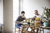 Homosexual couple using laptop and reading newspaper at breakfast table - CAVF44278