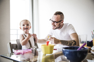 Happy father feeding daughter at breakfast table against wall - CAVF44287