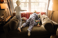 Brothers playing on sofa against window at home - CAVF44437