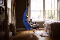 Boy reading book while sitting on swing in bedroom - CAVF44449