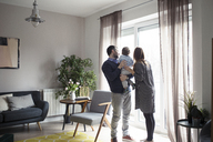 Loving parents with son looking through window while standing at home - CAVF44461