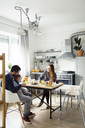 Parents with son having breakfast at table in kitchen - CAVF44467