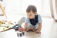 Baby boy playing with toys while sitting on floor at home - CAVF44476